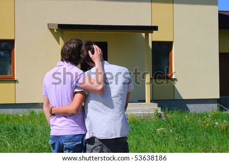 Same-sex couple standing in front of their new house - stock photo