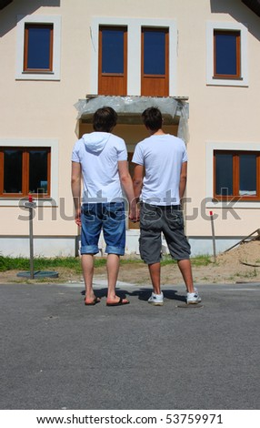 Same-sex couple standing in front of their new house