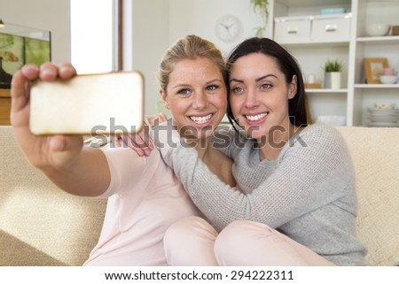 Same sex female couple taking a selfie using a mobile phone in their home - stock photo