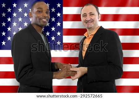 Same sex gay couple legally married in United States of America.  The interracial couple has an American flag in the background.