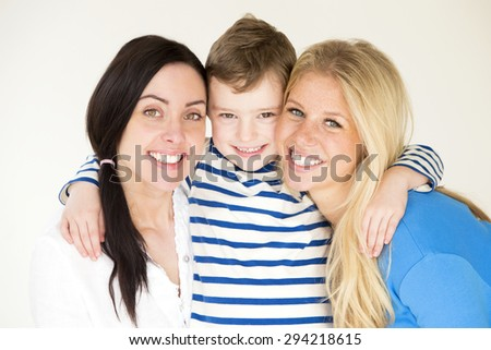 Same sex male couple smiling for the camera with their daughters at home.  - stock photo