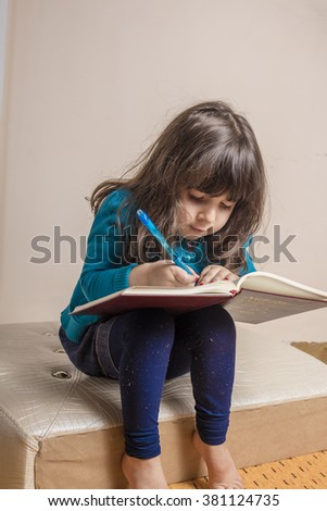 Samll girl inside studio with red copybook and blue pen in hand in hand - stock photo