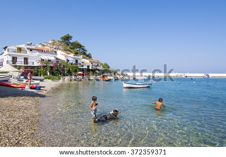 Samos Island, Greece - September 09, 2015 : Kids are playing with dog in Kokkari Beach. Kokkari Village is the most populer place in Samos Island.