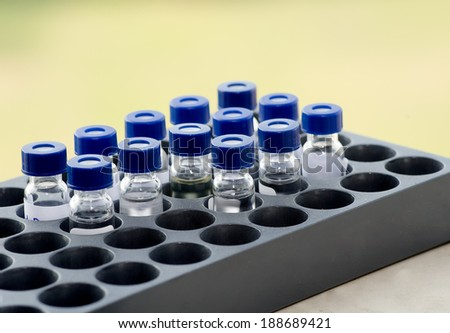 Sample vial in the instrumental analysis tray on blur green background - stock photo