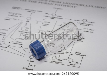 Sample vial on paper with chemical formula - stock photo