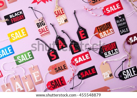 Samples of paper tags with strings and word sale on pink background