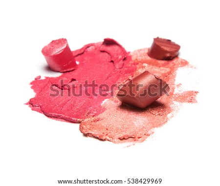 Samples of trendy make up product. Different colors of smeared and sliced lipstick on white textured surface. Close-up, shallow depth of field