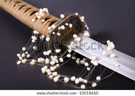 Samurai sword detail and pearls on black - stock photo