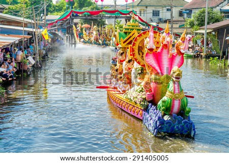 SAMUT PRAKAN,THAILAND-OCTOBER 18, 2013:The Lotus Giving Festival(Rap Bua) in Samut Prakan,Thailand. Devotees throw lotus flowers to boat procession that carry Buddha image on the end of Buddhist Lent. - stock photo