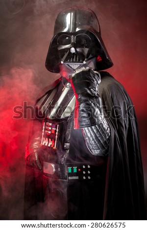 SAN BENEDETTO DEL TRONTO, ITALY. MAY 16, 2015. Portrait of Darth Vader costume replica with fist punch. Darth Vader is a fictional character of Star Wars saga.  Red backlight and smoke - stock photo