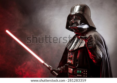 SAN BENEDETTO DEL TRONTO, ITALY. MAY 16, 2015. Portrait of Darth Vader costume replica with grab hand and his red sword. Lord Fener is a fictional character of Star Wars saga. Red backlight and smoke - stock photo