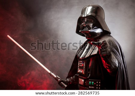 SAN BENEDETTO DEL TRONTO, ITALY. MAY 16, 2015. Portrait of Darth Vader costume replica with grab hand and  sword . Lord Fener is a fictional character of Star Wars saga.  Red grazing light and smoke - stock photo