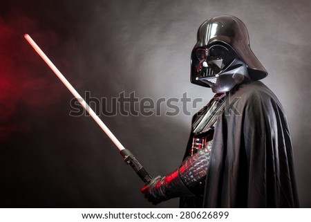 SAN BENEDETTO DEL TRONTO, ITALY. MAY 16, 2015. Portrait of Darth Vader costume replica with  his sword . Darth Vader is a fictional character of Star Wars saga.  Red grazing light and black background - stock photo