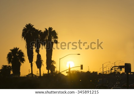 San Bernardino sunset golden glow of setting sun silhouettes palm trees and rush our traffic