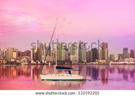 SAN DIEGO, CA - AUG 12, 2012:  San Diego, CA skyline at sunset as boat sails along The Coronado Bay on Aug 12, 2012. San Diego is the 2nd largest city in California. - stock photo