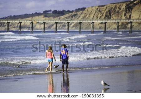 SAN DIEGO, CALIFORNIA - MARCH 31: A young couple enjoy walking on La Jolla Shores Beach on March 31, 2013 in San Diego, CA, USA. La Jolla Shores is a very popular vacation place in San Diego, CA. - stock photo