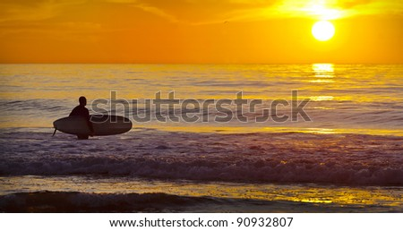 San Diego Surfer with Surf Board Wading into Ocean During Sunset - stock photo