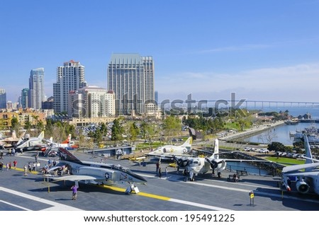 SAN DIEGO,USA - FEBRUARY 24 2014: The historic aircraft carrier, USS Midway, now a museum docked in Downtown San Diego, Southern California, United States of America, the skyline and Coronado bridge. - stock photo