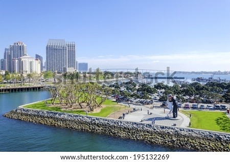 SAN DIEGO, USA - FEBRUARY 24 2014: The sculpture of unconditional surrender, of a sailor kissing a nurse after the end of world war II, the San Diego skyline and the Coronado bridge in the background. - stock photo
