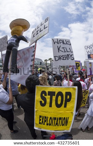 SAN DIEGO, USA - MAY 27, 2016: A Trump pinata and anti-Trump wall signs are held by an emotional Hispanic crowd at a protest outside a Trump rally in San Diego.