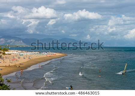 SAN FELICE CIRCEO, ITALY - SEPTEMBER 17, 2016: People enjoy the beautiful beach of S. Felice Circeo on the last days of Summer. Some are surfing.
