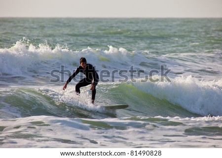 SAN FERNANDO, CADIZ, SPAIN - FEB 19: Unknown surfer taking waves on the 2nd championship of Surf and BodyBoard Impoxibol on Feb 19,2011 on the beach of Camposoto of San Fernando, Cadiz, Spain - stock photo