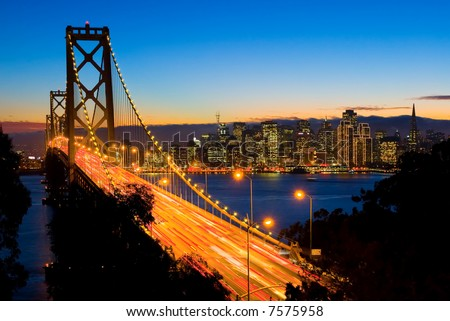 San Francisco and Bay Bridge at night with Christmas lights around the buildings - stock photo