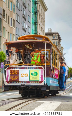 SAN FRANCISCO - APRIL 24: Famous cable car with people at a steep street on April 24, 2014 in San Francisco, California. The cable car system forms part of the intermodal urban transport network. - stock photo