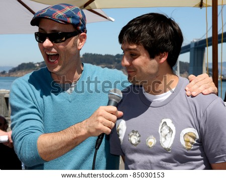 SAN FRANCISCO - AUGUST 27: Olympic gold medalist Brian Boitano (L) interviews the unidentified winner in oyster-eating contest at OysterFest, annual benefit for Surfrider Foundation on August 27, 2011 in San Francisco, CA.