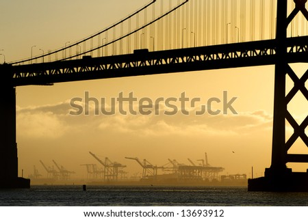 San Francisco Bay bridge and polluting industrial barges  at sunrise - stock photo