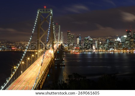 San Francisco Bay Bridge and skyline at night with city lights - stock photo