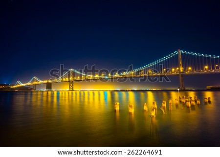 San Francisco Bay Bridge at Night.  Lights reflecting on the water. - stock photo