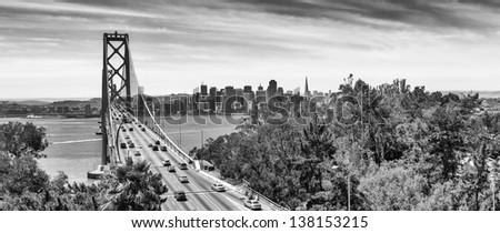 San Francisco Bay Bridge with the city skyline in the background. Panorama in black and white. - stock photo