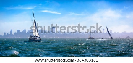 San Francisco Bay on a windy stormy day. Sailboats out in rough water. Skyline is visible through the fog. Panorama - stock photo