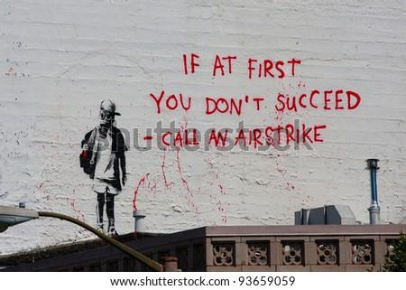 SAN FRANCISCO, CA - CIRCA MAY 2010: Stencil graffiti piece by Banksy on a building on a corner of Columbus St and Broadway St, circa May 2010 in San Francisco, CA - stock photo