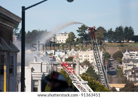 SAN FRANCISCO, CA - DECEMBER 22: Firefighter pouring water on a burning building on the corner of Golden Gate Ave and Pierce St in Western Addition district December 22, 2011 in San Francisco CA