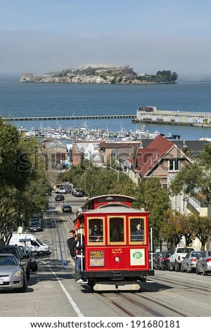 SAN FRANCISCO, CA - FEB. 28, 2013: A View of Cable Car and Alcatraz Island, both are the icons at the Bay Area in San Francisco, California. - stock photo