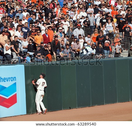 SAN FRANCISCO, CA - JULY 28: Giants Vs Marlins: Aubrey Huff presses into the wall as he Watches a home run fly over his head left field at AT&T Park July 28, 2010 San Francisco, California. - stock photo