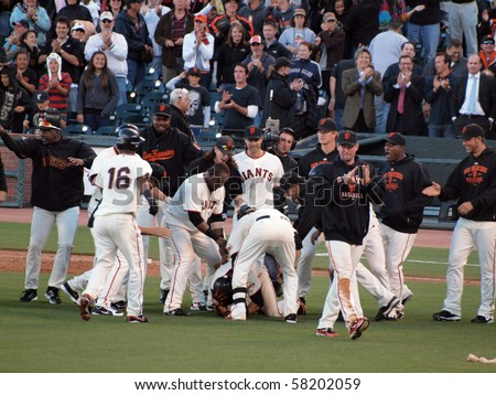 SAN FRANCISCO, CA - JULY 28: Giants Vs. Marlins: Giants Andres Torres get piled by teammates as they tap him on the helmet after winning hit.  July 28, 2010 ATT Park San Francisco California. - stock photo