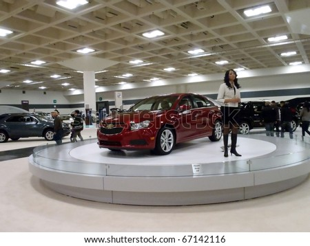 SAN FRANCISCO, CA - NOVEMBER 20: Lady discusses features of the Chevy Cruze on a spinning display platform at the 53rd International Auto Show November 20 2010 San Francisco. - stock photo
