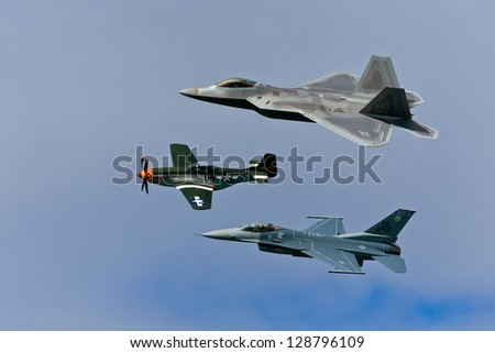 SAN FRANCISCO, CA - OCTOBER 5: P-51 Mustang WW II and modern F-16C Fighting Falcon and USAF F-22 Raptor aircrafts perform heritage flight during Fleet Week in San Francisco, CA on October 5, 2012 - stock photo