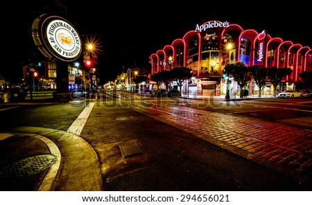 San Francisco, CA, USA - June 25th, 2015: Famous Fisherman's Wharf street and signage at night and Applebee's restaurant. - stock photo