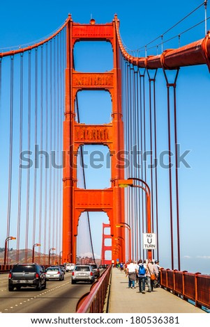 SAN FRANCISCO, CA, USA - SEPT 10: Cars and people crossing Golden Gate Bridge on September 10, 2013. The iconic Golden Gate Bridge was built over Francisco Bay and the Pacific Ocean in 1937. - stock photo