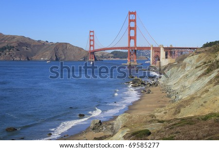 SAN FRANCISCO, CALIFORNIA: Golden Gate Bridge taken from overlook near Battery Crosby overlooking Marshall Beach as sailboat passes under bridge. - stock photo
