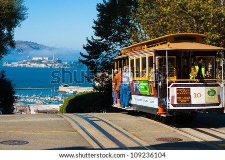 San Francisco, California - September 21, 2011: Powell Hyde cable car, an iconic tourist attraction, descending a steep hill peak overlooking Alcatraz prison island and the bay