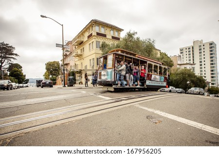 SAN FRANCISCO - JULY 26: Passengers enjoy a ride in a cable car on July 26, 2012 in San Francisco. It is the oldest mechanical public transport in San Francisco which is in service since 1873. - stock photo