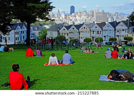 """SAN FRANCISCO - MARCH 30, 2014: Locals picnic while tourists take in the view from Alamo Park. The famous """"Painted Ladies"""" houses are in the foreground below the impressive skyline of the city. - stock photo"""