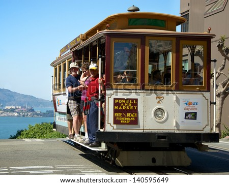 SAN FRANCISCO, MAY 2 - Unidentified people traveling in a cable car with Alcatraz visible in background, May 2, 2013, San Francisco, United States. - stock photo