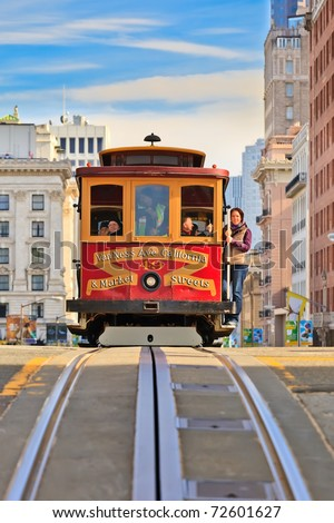 SAN FRANCISCO - NOV 26: Passengers enjoy a ride in a cable car on Nov 26, 2010 in San Francisco. It is the oldest mechanical public transport in San Francisco which is in service since 1873. - stock photo