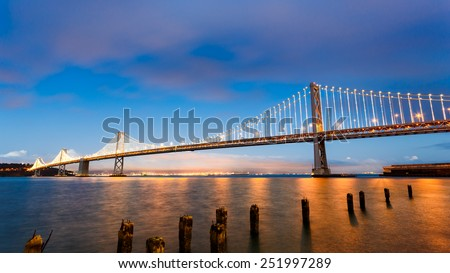 San Francisco-Oakland Bay Bridge illuminated at sunset - stock photo